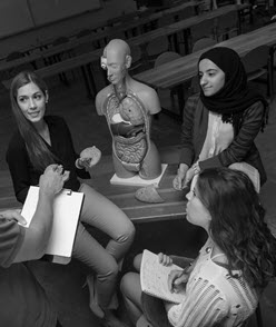 Three students and an anatomical model