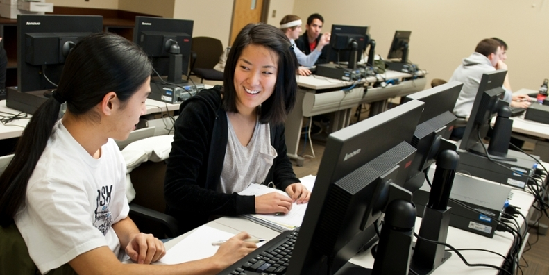 Two female students in a computer lab.