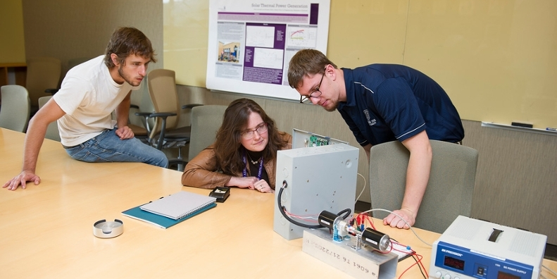 Two students and a professor working on equipment in a lab