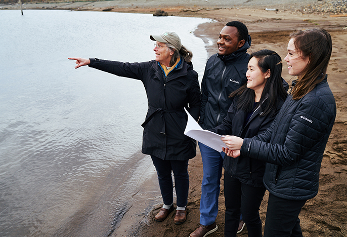 students and professor stand beside body of water